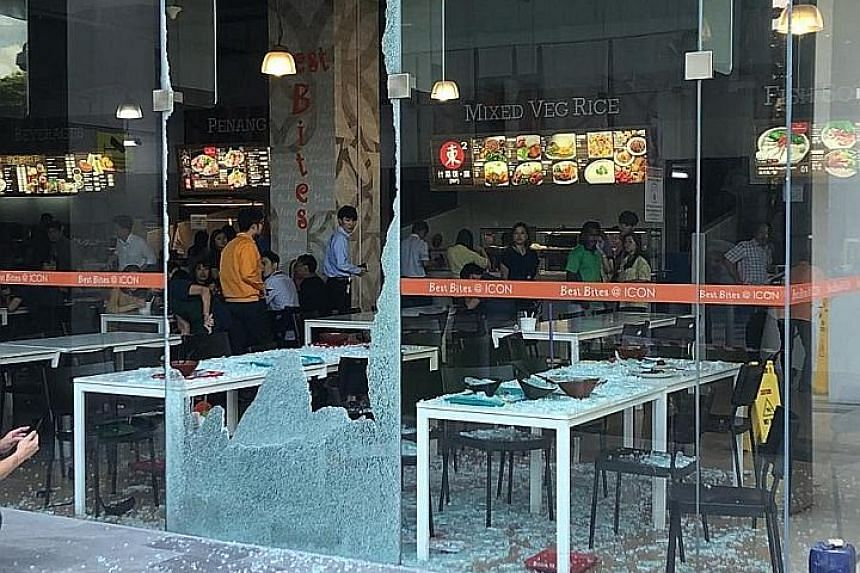 The shattered glass panel at the foodcourt of Icon@IBP. One person was taken to hospital and was discharged on the same day, while the other five suffered minor injuries.