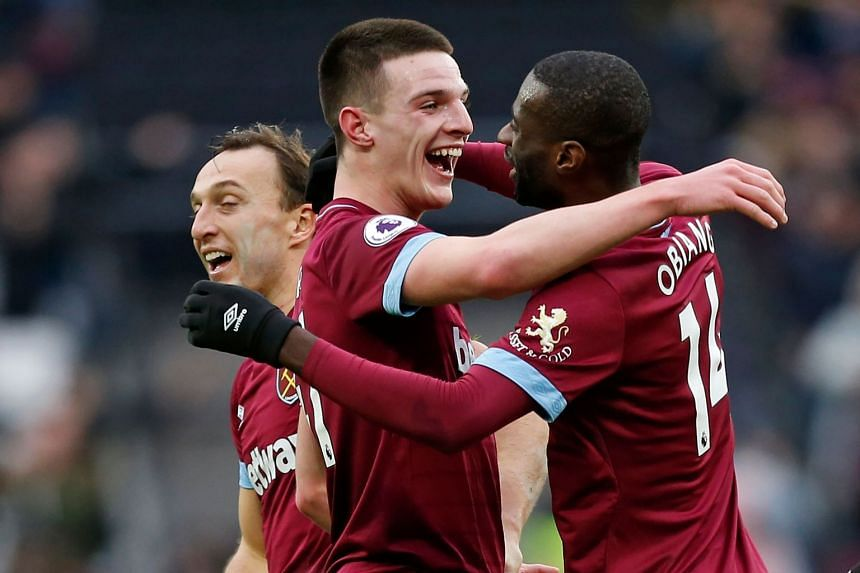 Rice (centre) and Pedro Obiang (right) embrace as West Ham players celebrate after the match.