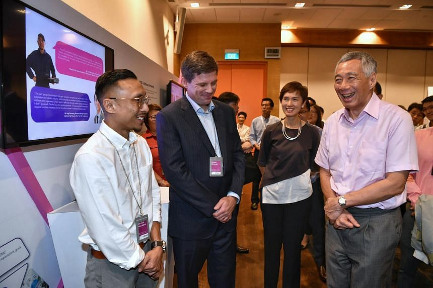 PM Lee Hsien Loong and Manpower Minister Josephine Teo chat with Mr Shawn Rimmel and Mr Md Faizal Abu Bakar from Global Automation Technologies.