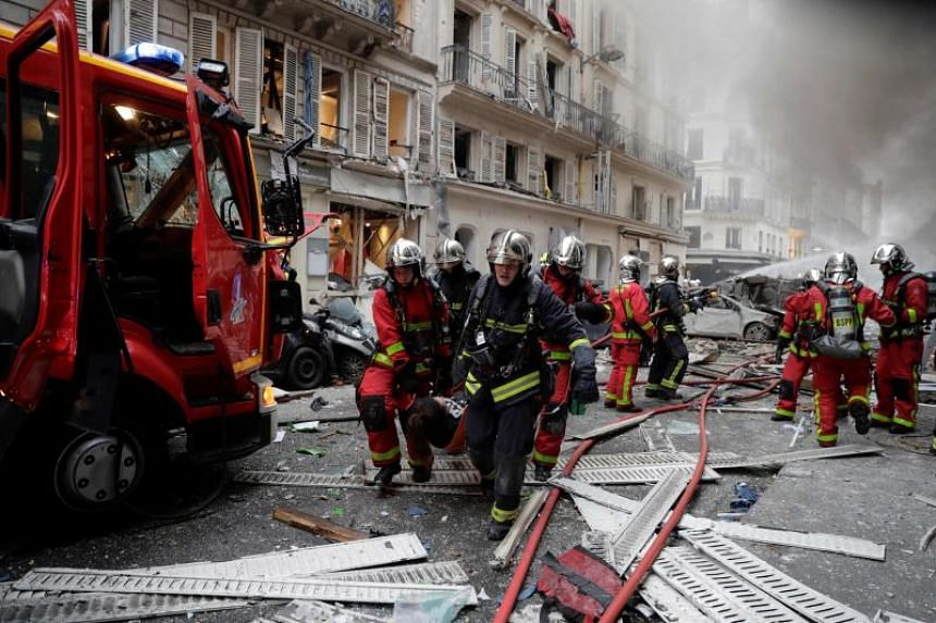 Firefighters evacuate an injured person on a stretcher after an explosion at a bakery in central Paris, on Jan 12, 2019.
