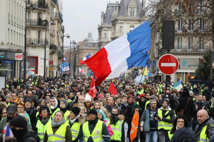 Demonstrators wave a giant French national flag as they march in Paris, on Jan 12, 2019, during an anti-government demonstration called by the Yellow Vest movement.