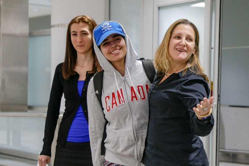 Qunun (centre) accompanied by Freeland (right) and refugee agency official Saba Abbas arrives in Toronto.