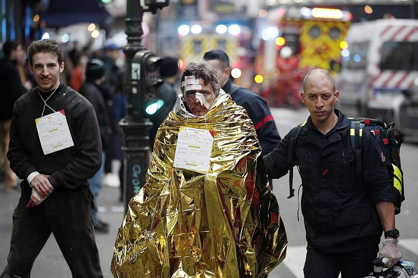 A huge explosion, probably caused by a gas leak, gutted the ground floor of a building in a central Paris shopping district yesterday, killing four people and injuring 47 others, the authorities said. Emergency staff helped victims (right) as police