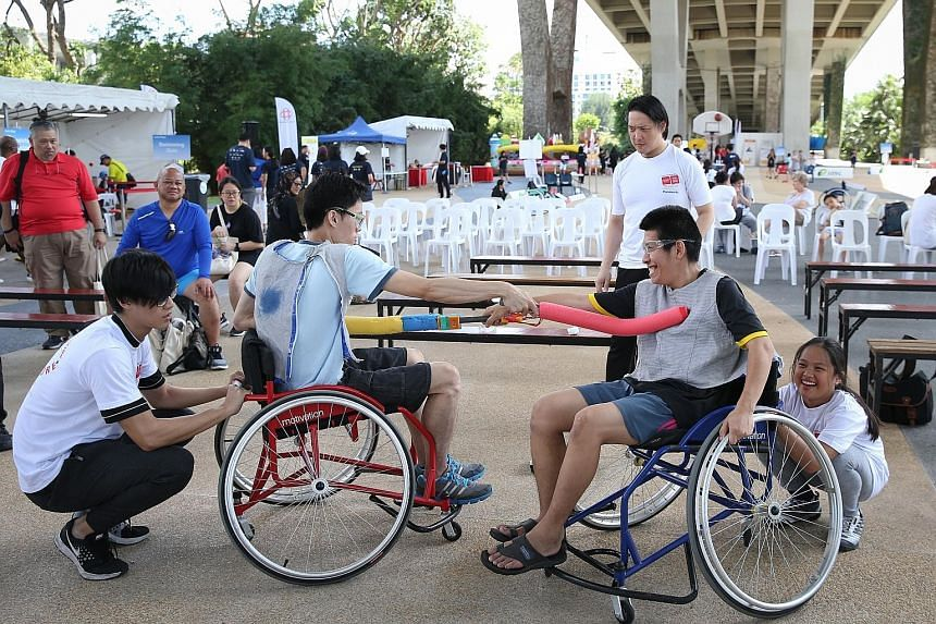 Pek Dewei (left), 30, and Oh Fu Quan, 28, trying out wheelchair fencing, among other activities, at Let's Play! At Passion Wave@Marina Bay. About 500 attended the first in a series of carnivals for people of all abilities that aims to promote a more