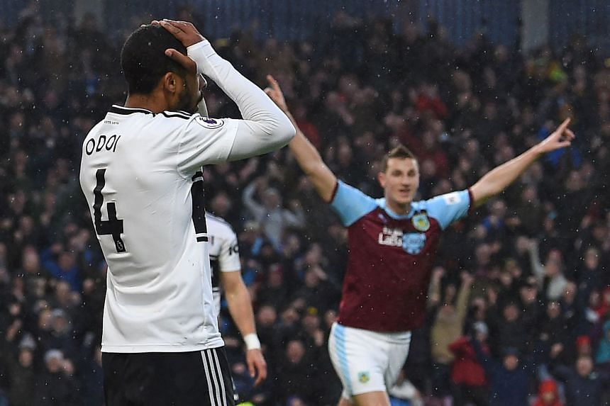 Burnley striker Chris Wood (right) reacts after Fulham's Denis Odoi (left) scores their second own-goal.
