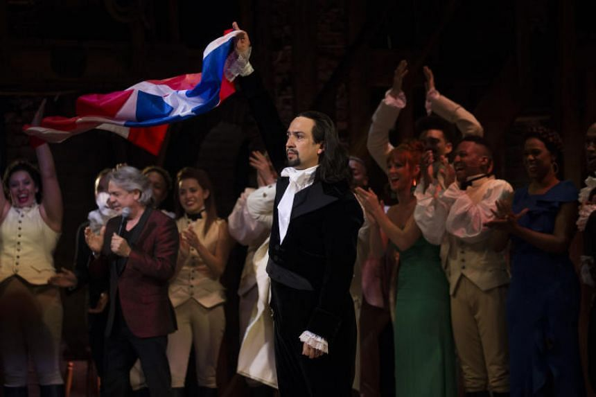 Lin-Manuel Miranda raises the Puerto Rican flag after the sold-out opening-night performance of the Broadway musical Hamilton in San Juan, Puerto Rico.