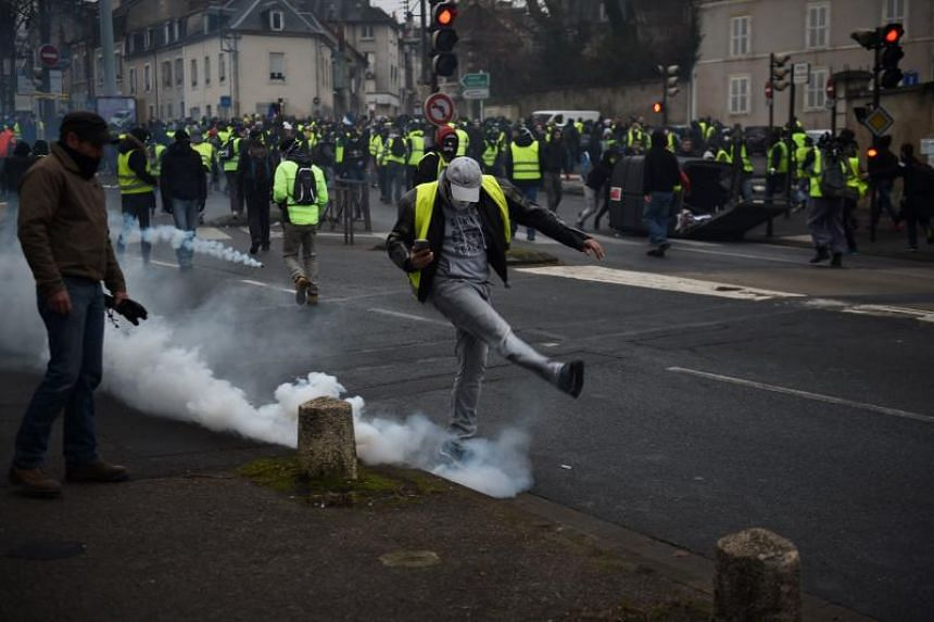 "A protester kicks a tear gas canister during an anti-government demonstration called by the ""Yellow Vest"" movement in Bourges, central France, on Jan 12, 2019."