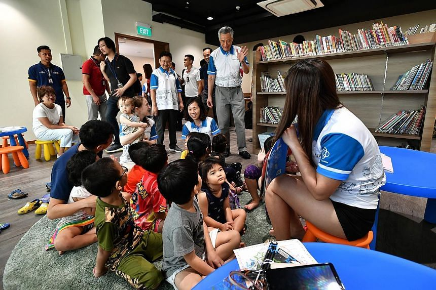 Prime Minister Lee Hsien Loong greeting children and residents taking part in a KidsRead programme at a mini library in Teck Ghee Community Club yesterday. The upgraded CC in Ang Mo Kio reopened in August last year, two years after it closed for reno