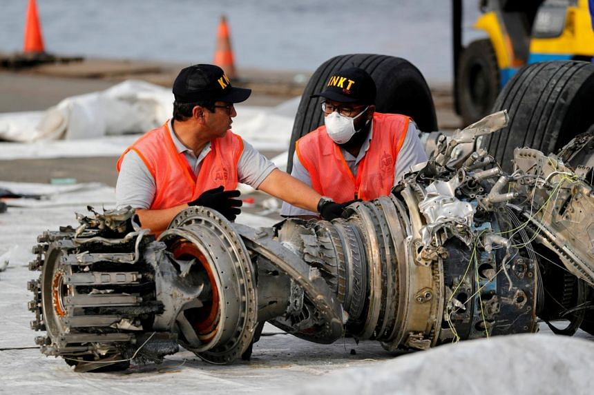 Indonesian National Transportation Safety Commission (KNKT) officials examine a recovered turbine engine from the Lion Air flight JT610 at Tanjung Priok port in Jakarta, on Nov 4, 2018.