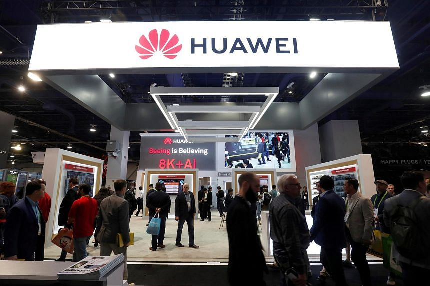 Attendees pass by a Huawei booth during the 2019 CES in Las Vegas, Nevada, US, on Jan 9, 2019.