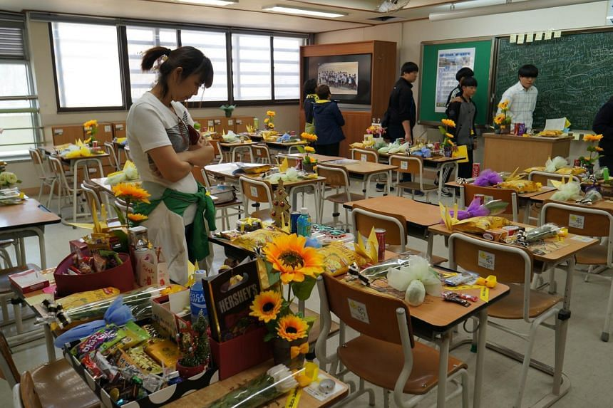 A file photo taken on April 11, 2015, shows visitors looking at desks belonging to the student victims of the Sewol ferry sinking disaster at Danwon High School in Ansan, South Korea.