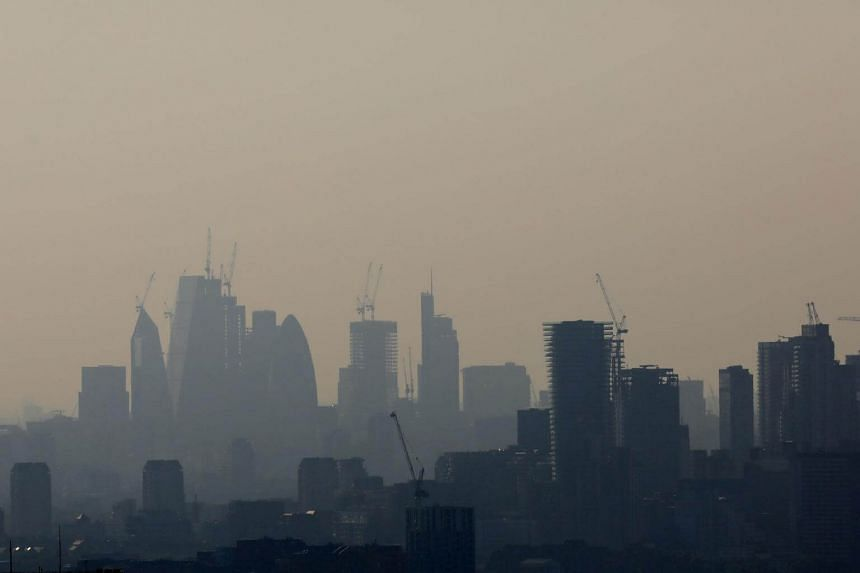 Buildings and construction cranes are seen through a heat haze in London, Britain, on May 6, 2018.