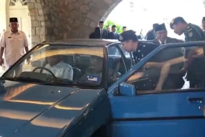Screengrab from a video shows Johor Menteri Besar Osman Sapian (second from right) being stopped by a man from riding with Sultan Ibrahim Ibni Almarhum Sultan Iskandar and Prime Minister Mahathir Mohamad in a car.