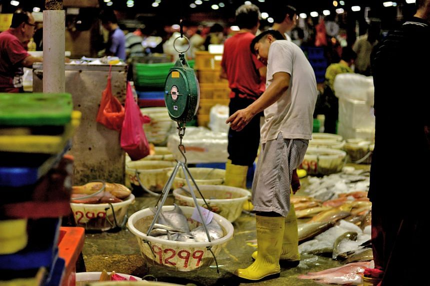 A worker weighing fish at the Jurong Fishery Port. Supermarket chain NTUC FairPrice says that the varieties of fish that are more popular during Chinese New Year, like red grouper, snapper, threadfin and pomfret, cost 10 to 15 per cent more now compa