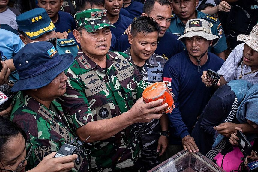 Indonesian navy commander Rear-Admiral Yudo Margono holding the cockpit voice recorder that was recovered yesterday.