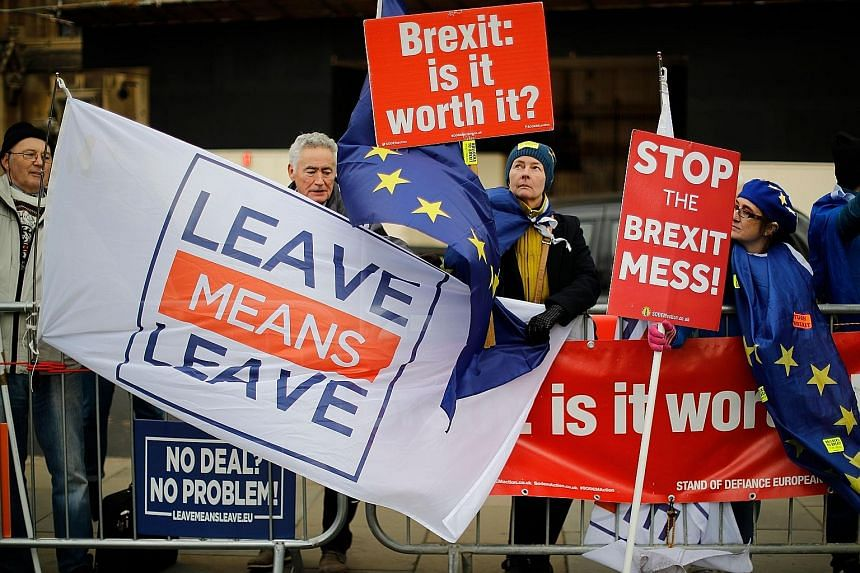 Pro and anti-Brexit supporters demonstrating outside the Houses of Parliament in London yesterday, as Prime Minister Theresa May warned MPs against failing to deliver Brexit.