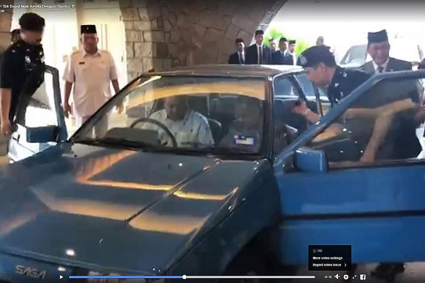 The video clip shows Johor Menteri Besar Osman Sapian trying to get into the Proton Saga as an officer helps Prime Minister Mahathir Mohamad with his seat belt.