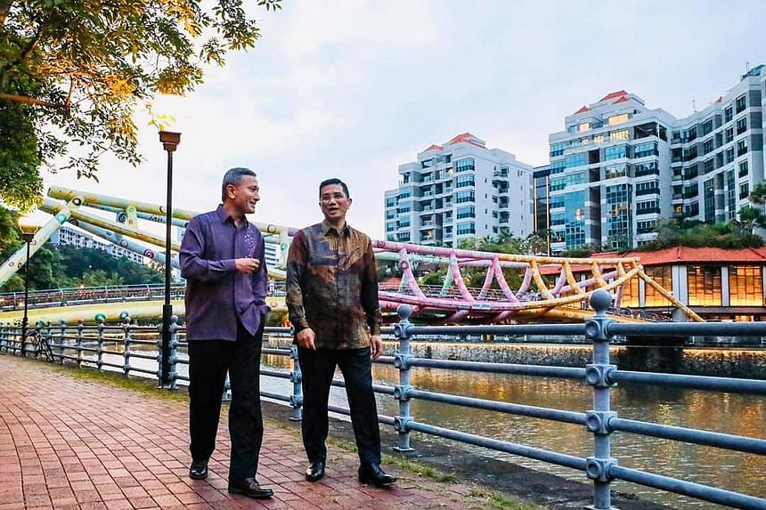 """Foreign Minister Vivian Balakrishnan and Malaysia's Economic Affairs Minister Azmin Ali taking a stroll along the Singapore River after dinner on Sunday. Dr Balakrishnan said they had """"an open and candid discussion of the issues currently confronting"""