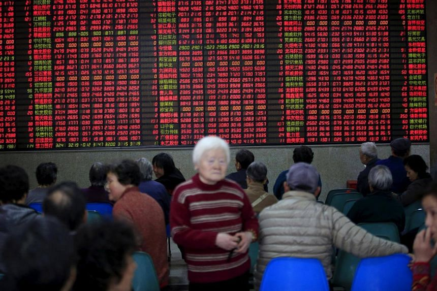 Investors look at an electronic board showing stock information at a brokerage house in Shanghai, China.