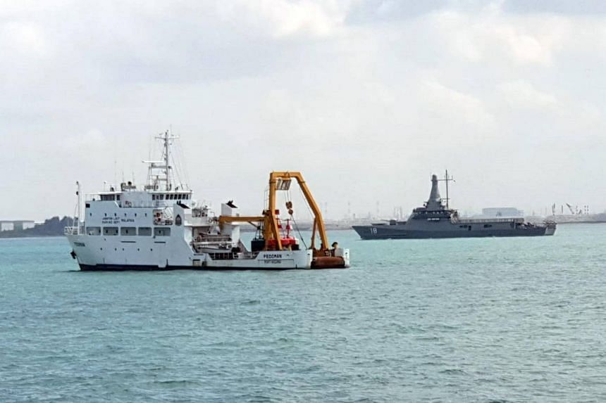 Republic of Singapore Navy littoral mission vessel RSS Justice (right) and the Malaysian Marine Department vessel MV Pedoman, which was anchored within Singapore port limits.
