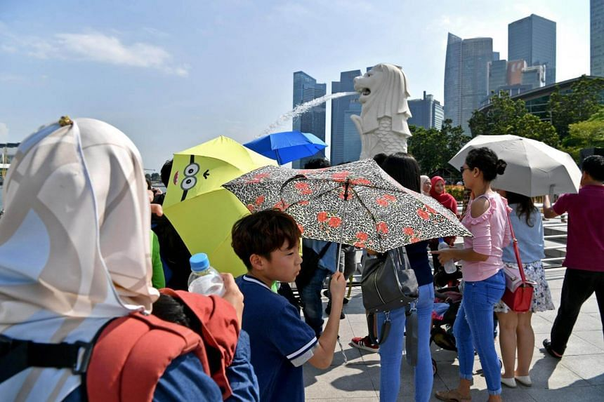 Umbrellas, cover-all scarves and water bottles were out in full force as visitors to the Merlion Park braved a hotter-than-usual December in Singapore in 2018.