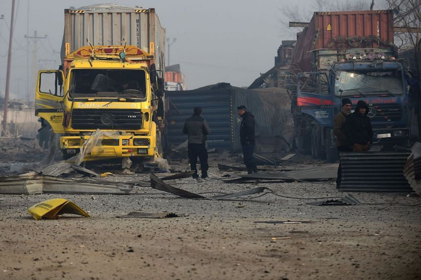 Afghan private security guards investigate the site of a powerful truck bomb attack a day after it detonated near a foreign compound in Kabul, on Jan 15, 2019.