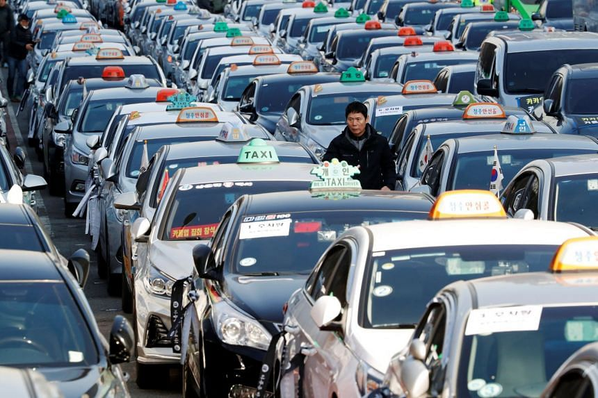 A taxi driver walks amid parked taxis to protest against Kakao Mobility's proposed car-sharing service in Seoul on Dec 20, 2018. Kakao Mobility said it would re-enter talks over its proposed car-sharing service with an open mind, and would even consi