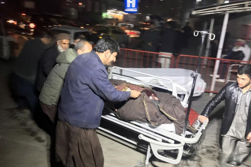 Afghan health workers carry an injured man to the emergency hospital after a car bomb blast targeted a foreigner camp in Kabul, Afghanistan, on Jan 14, 2019.