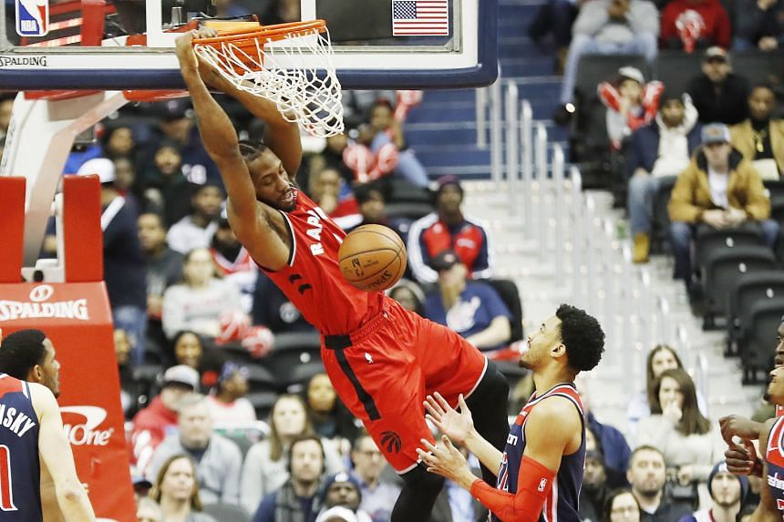 Toronto Raptors forward Kawhi Leonard hanging on to the rim after a dunk over Washington Wizards forward Otto Porter Jr. The Raptors, who improved to a league-leading 33-12, racked up their fifth straight win.