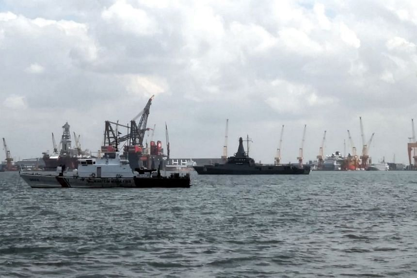 Republic of Singapore Navy littoral mission vessel RSS Justice (right) and Malaysian Maritime Enforcement Agency vessel KM Marudu (far left), which was anchored within the Singapore port limits.