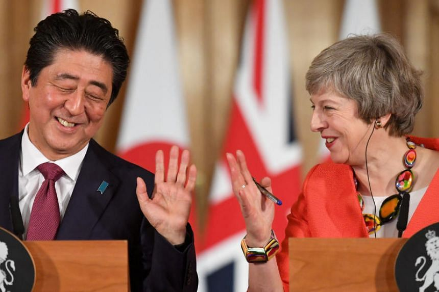 British Prime Minister Theresa May and Japanese Prime Minister Shinzo Abe hold a news conference after a bilateral meeting in London on Jan 10, 2019.