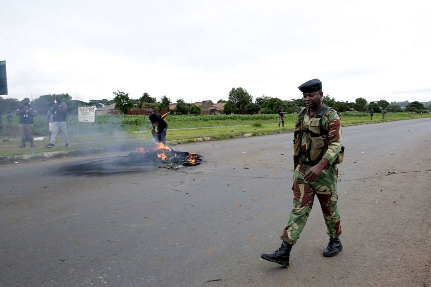 An armed soldier walks past smoke coming from burning tyres left by protesters in Harare.