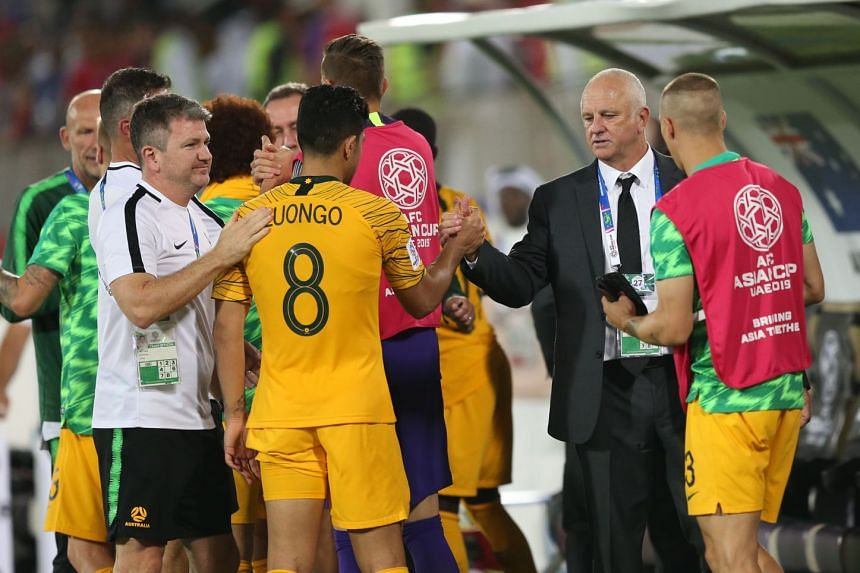 Australia head coach Graham Arnold (second right) celebrates with players after winning the match.