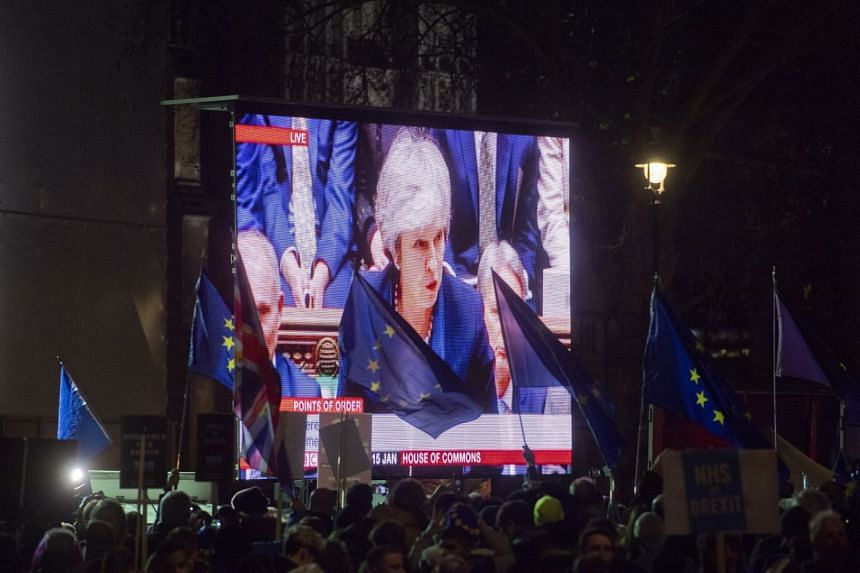 Protesters' flags flutter as Britain's Prime Minister Theresa May makes a statement on a video screen outside the Houses of Parliament after being defeated in the vote on Brexit.