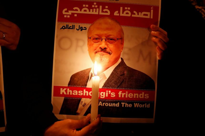A demonstrator holds a poster featuring Jamal Khashoggi outside the Saudi Arabia consulate.
