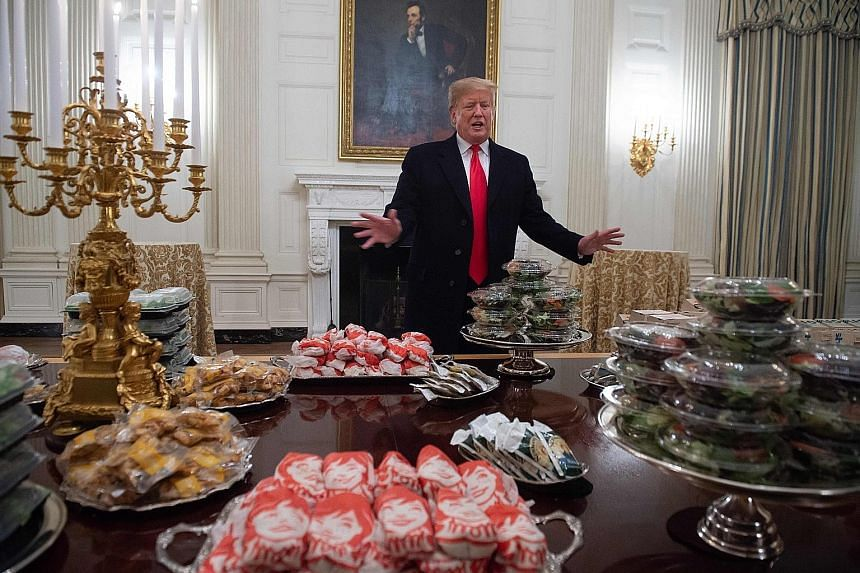 US President Donald Trump speaking in front of a spread of fast food he ordered for a ceremony honouring the Clemson Tigers football team in the State Dining Room of the White House on Monday. With the US government shutdown, about 800,000 federal em