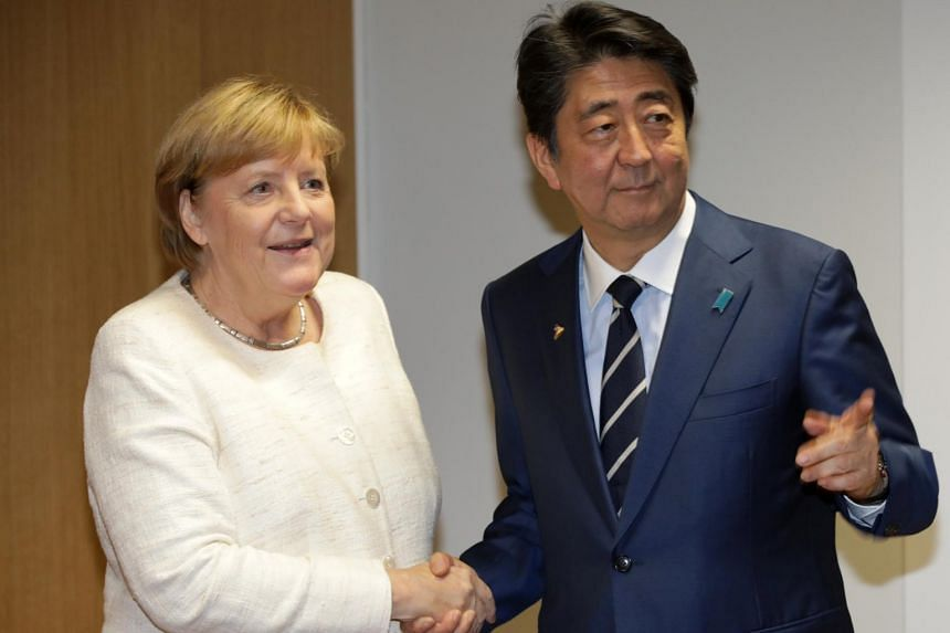 Japan's Prime Minister Shinzo Abe with German Chancellor Angela Merkel on the sidelines of the Asem leaders summit in Brussels, Belgium, on Oct 18, 2018.
