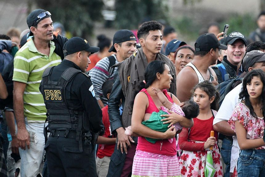 A Guatemalan policeman looks at Honduran migrants heading to the United States with a second caravan on Jan 15, 2019.