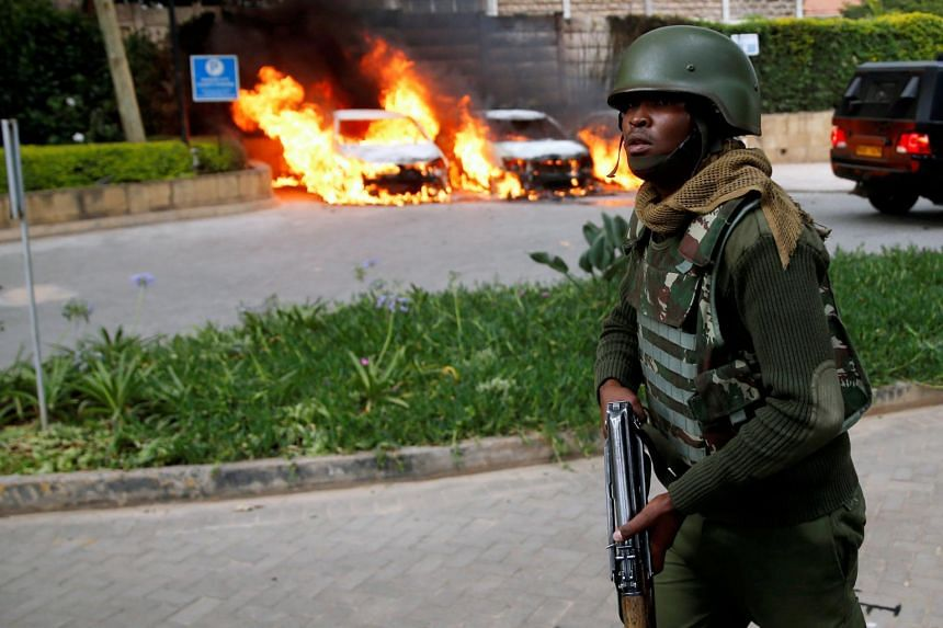 A policeman runs past burning cars at the scene where explosions and gunshots were heard at the Dusit hotel compound in Nairobi, Kenya on Jan 15, 2019.