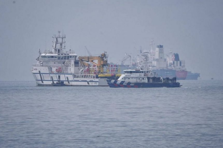 A Singapore Police Coast Guard vessel (centre) passes a Malaysian government vessel (left) in the waters between Singapore and Malaysian, on Dec 6, 2018.