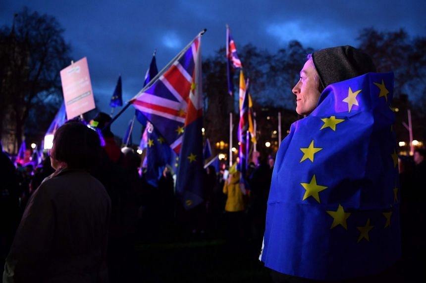 An anti-Brexit activist wrapped in an EU flag stands with other protesters as they demonstrate outside of the Houses of Parliament in central London.