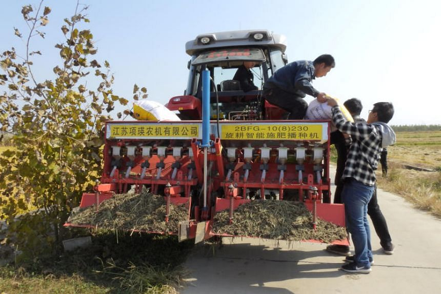 Staff members load fertiliser onto an automated tractor near a field in Xinghua, Jiangsu province, China, on Oct 30, 2018.