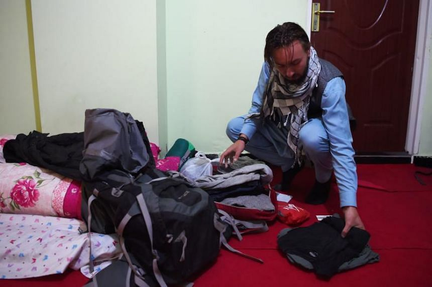 Dutch tourist Ciaran Barr, arranges his clothes as he is hosted by his Afghan Couchsurfing host at a house in Kabul on Nov 11, 2018.