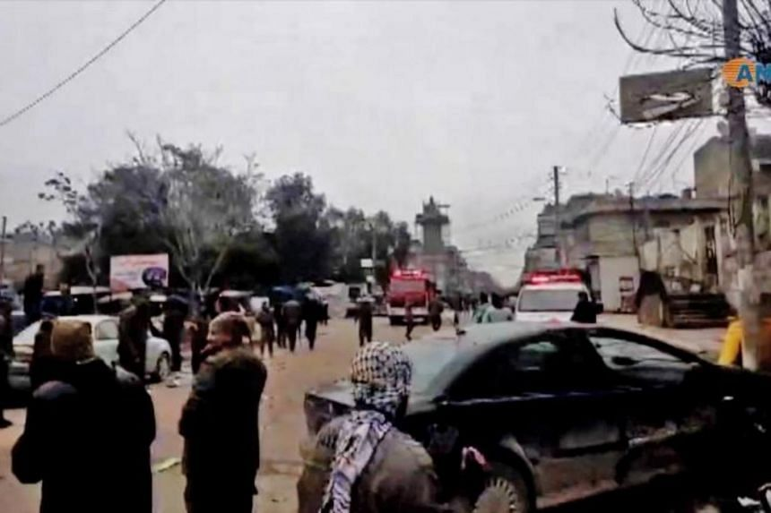 People gathered at the scene of a suicide attack in the northern Syrian town of Manbij, in an image grab taken from a video published by Hawar News Agency on Jan 16, 2019.
