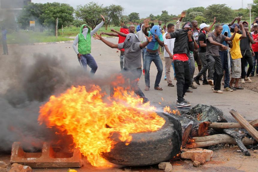 Protesters stand behind a burning barricade during protests on a road leading to Harare, Zimbabwe, on Jan 15, 2019.