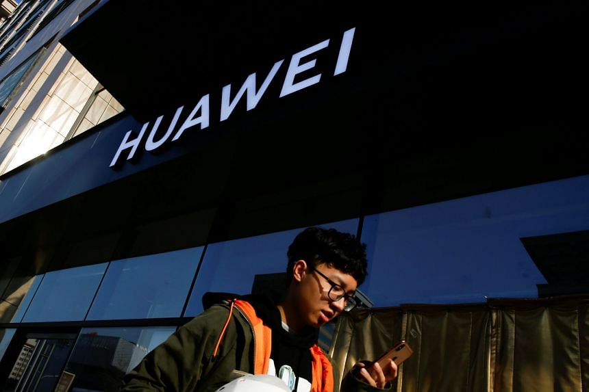 A man uses his phone as he walks past a Huawei shop in Beijing, China.