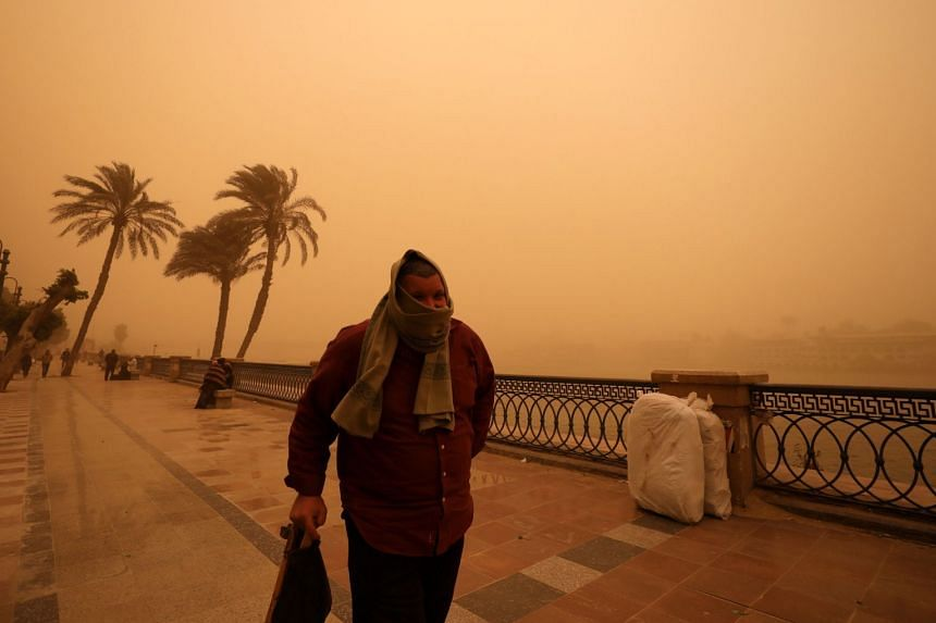 A man covers his face during a sandstorm near the River Nile in Cairo.