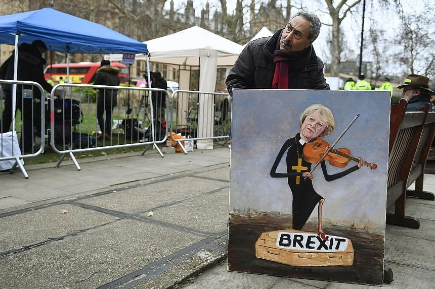 A man in London with a painting yesterday depicting British Prime Minister Theresa May after Parliament rejected her Brexit deal.