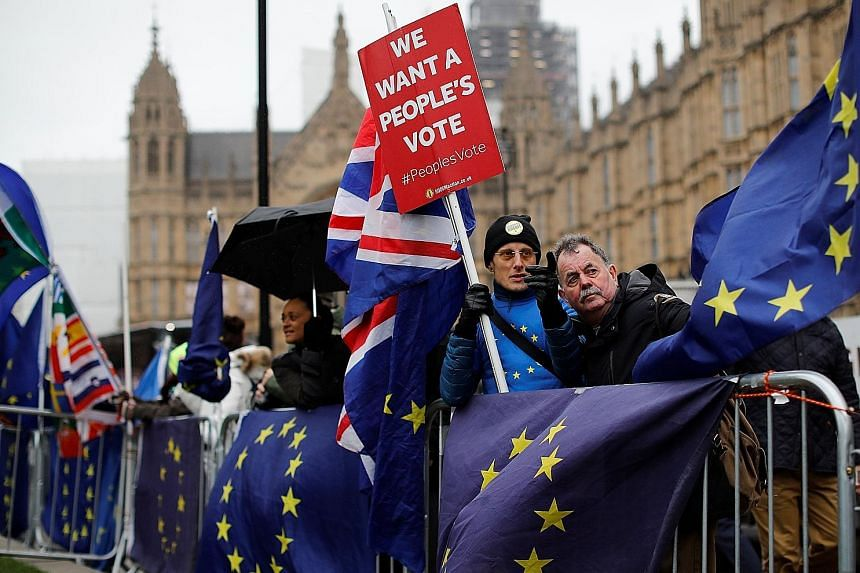Anti-Brexit activists outside Parliament in London yesterday, after lawmakers voted 432 to 202 against British Prime Minister Theresa May's Brexit deal, the country's worst parliamentary defeat in modern history.
