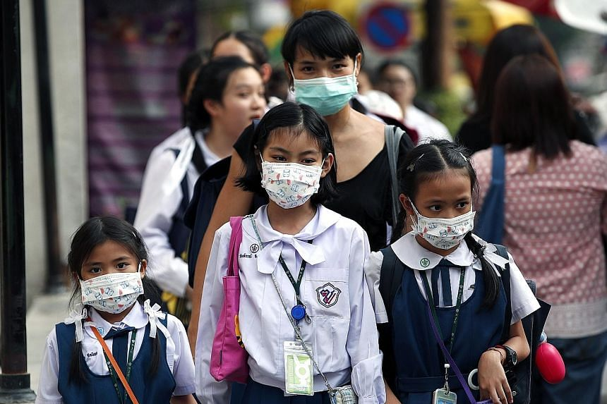 People wearing face masks in Bangkok on Tuesday as the air quality in the Thai capital soared to unhealthy levels.
